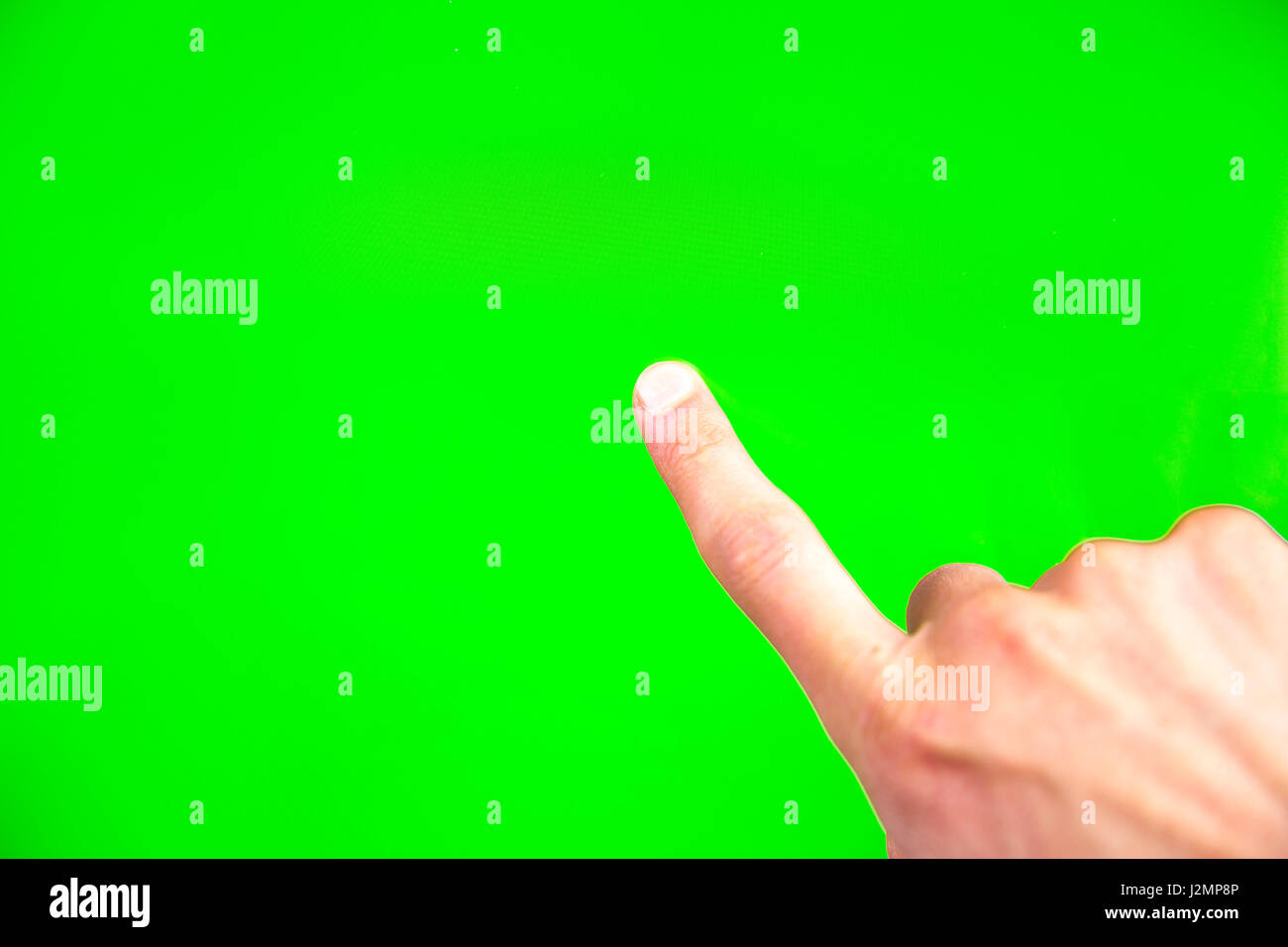 Young man types and slides on a computer screen. Digital screen with chroma key screen - green screen. Male hand. - Stock Image