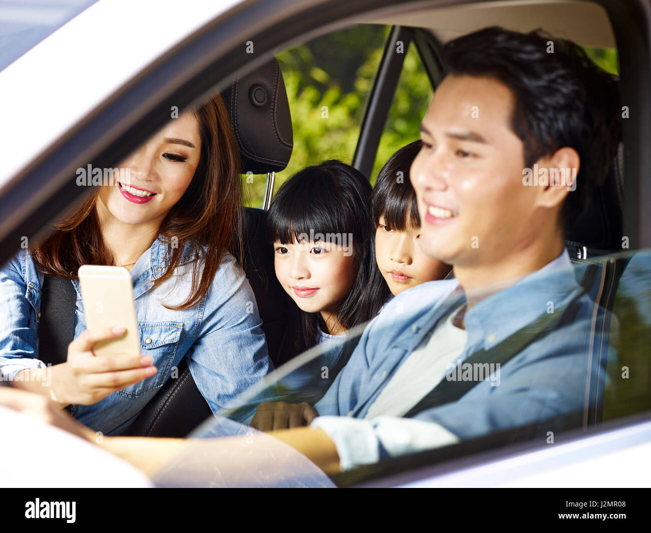 happy asian family with two children traveling by car, mother using cellphone while father driving, focus on the - Stock Image