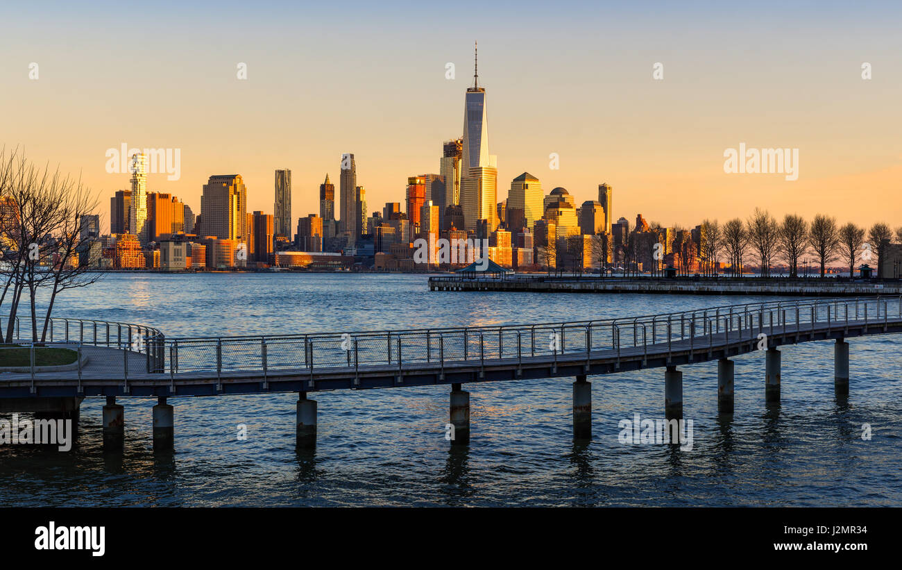 New York City Financial District skyscrapers at sunset from the Hudson River. Lower Manhattan skyline and pedestrian - Stock Image