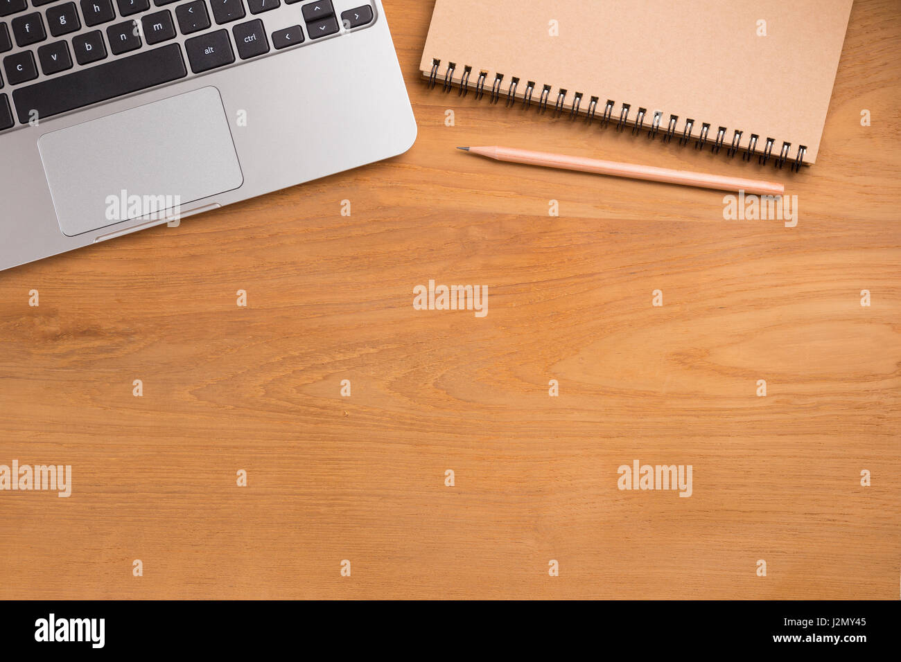 Portable computer laptop, pencil, paper notebook on wooden table - Stock Image