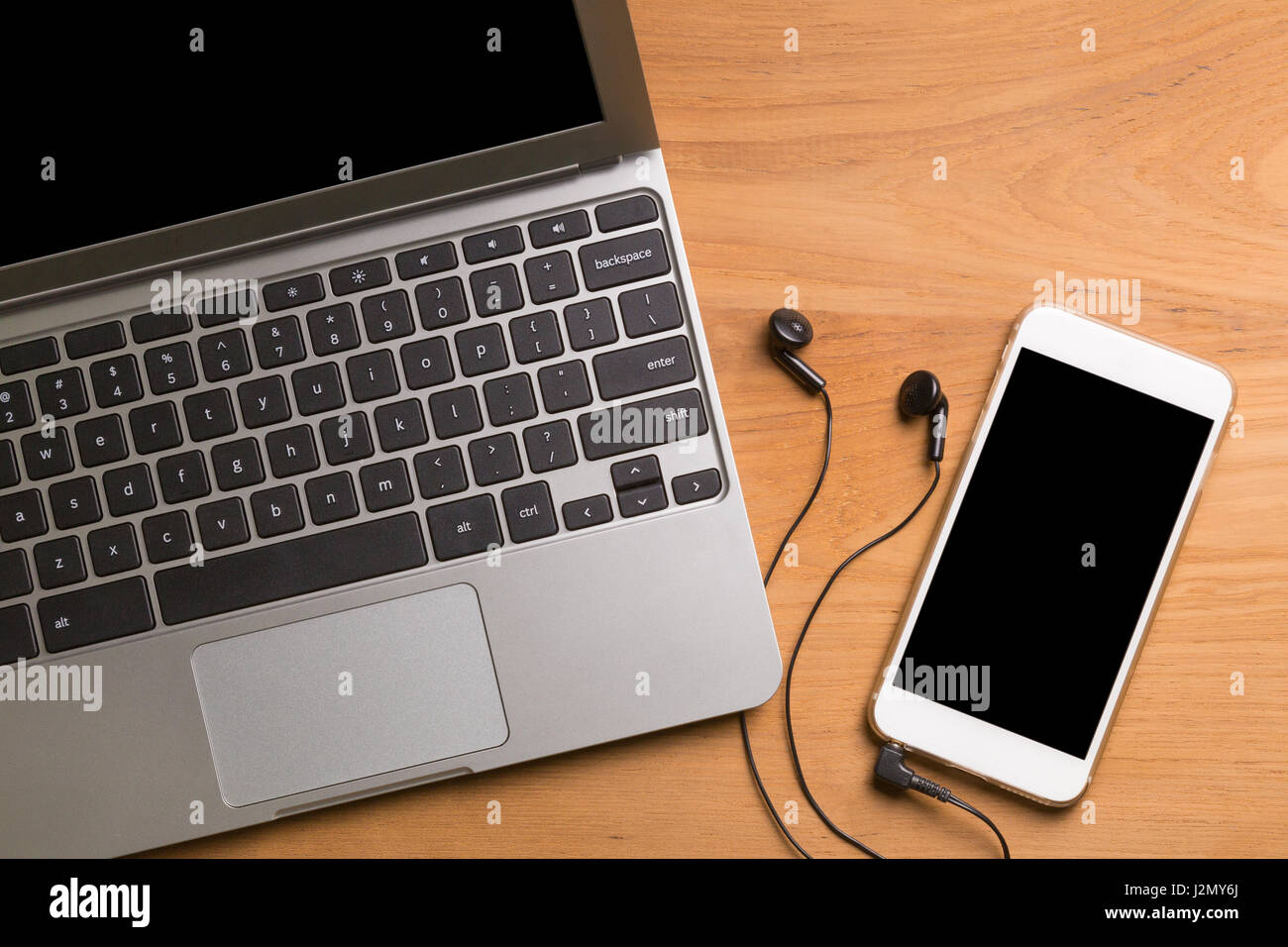 Portable computer laptop, smartphone, earphones, on wood table - Stock Image