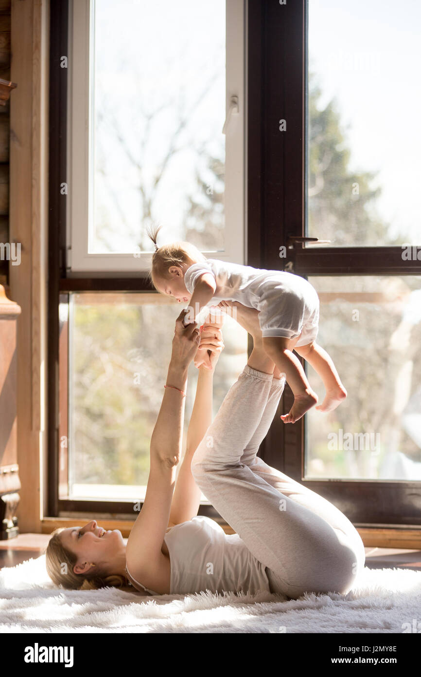Young attractive sporty mother working out with her baby daughter, exercising at home wearing white sportswear, - Stock Image