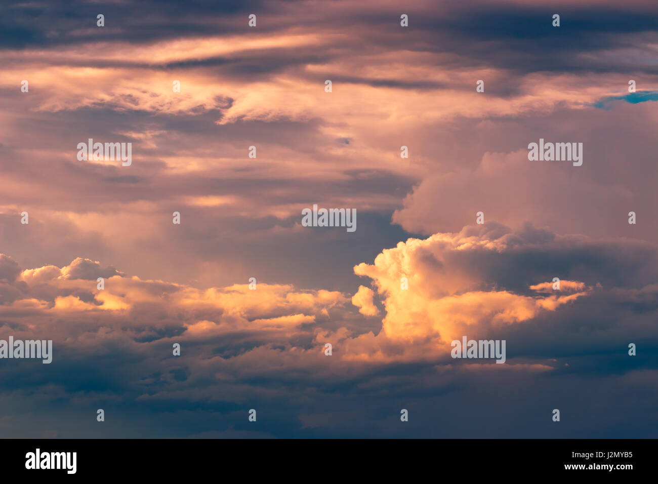 Orange fluffy patches of clouds against deep blue sky at sunset, color enhanced - Stock Image