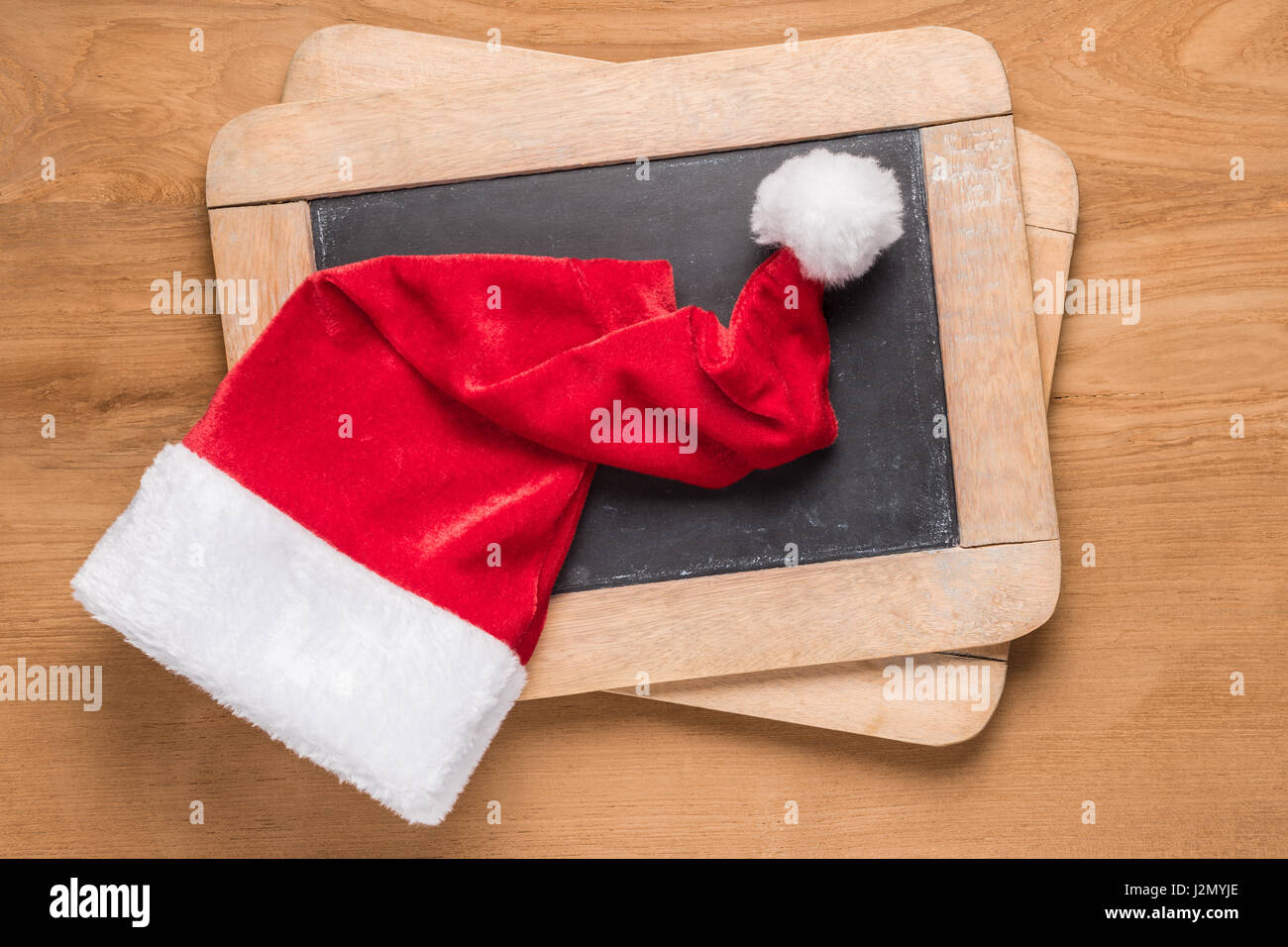 Small Santa Christmas hat on top of small chalk blackboards on wooden desk - Stock Image