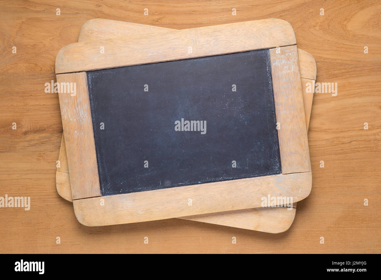 Small chalk blackboards on wooden desk, empty with room for copyspace text - Stock Image
