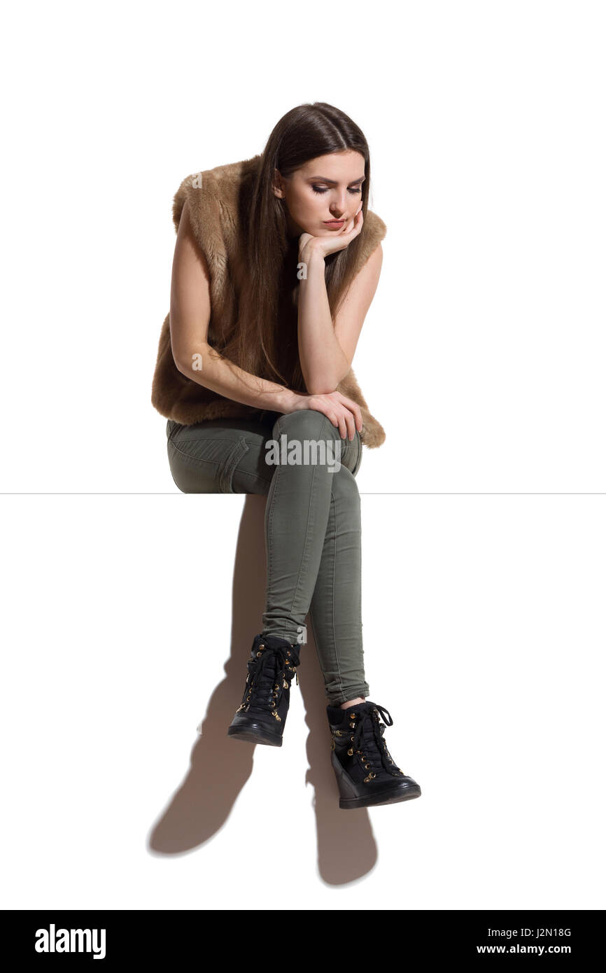 Sad young woman in brown fur waistcoat and khaki pants sitting on a top with legs crossed and looking down. Full - Stock Image