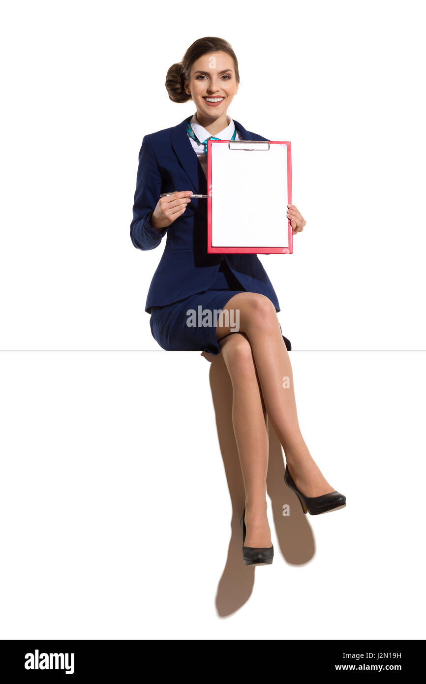Elegant woman in blue suit and black high heels, sitting on a top with legs crossed, holding red clipboard pointing - Stock Image