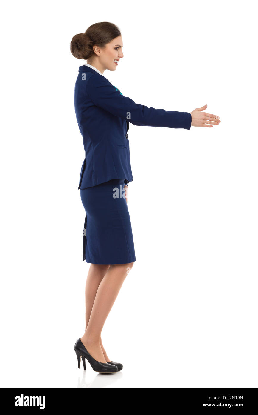Young woman in blue formalwear and high heels, standing and giving hand for a handshake. Side view. Full length - Stock Image