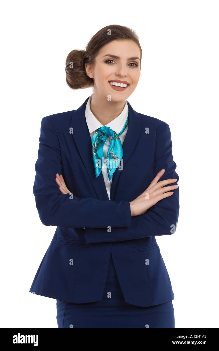 Smiling beautiful woman in blue suit and turquoise scarf posing with arms crossed and looking at camera. Waist up - Stock Image