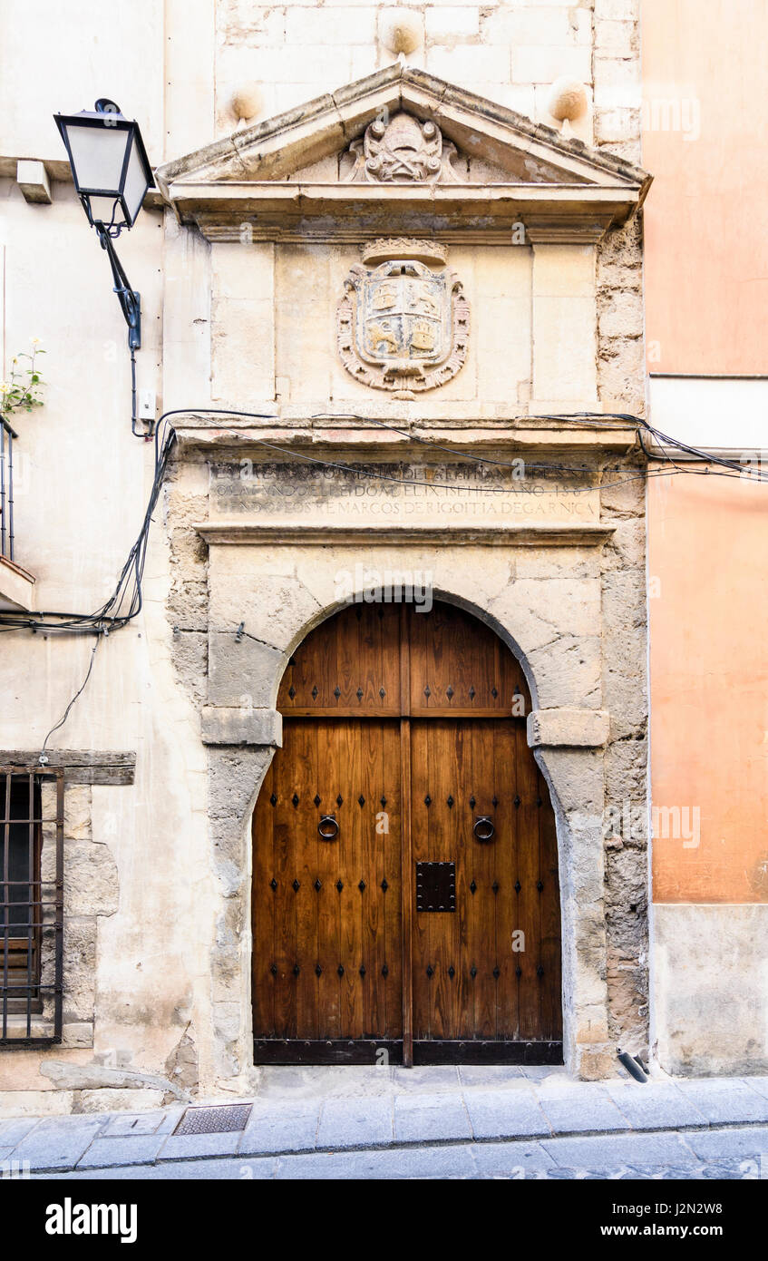 Old wooden double doors below a triangular pediment and coat of arms on a historic building in the medieval town - Stock Image