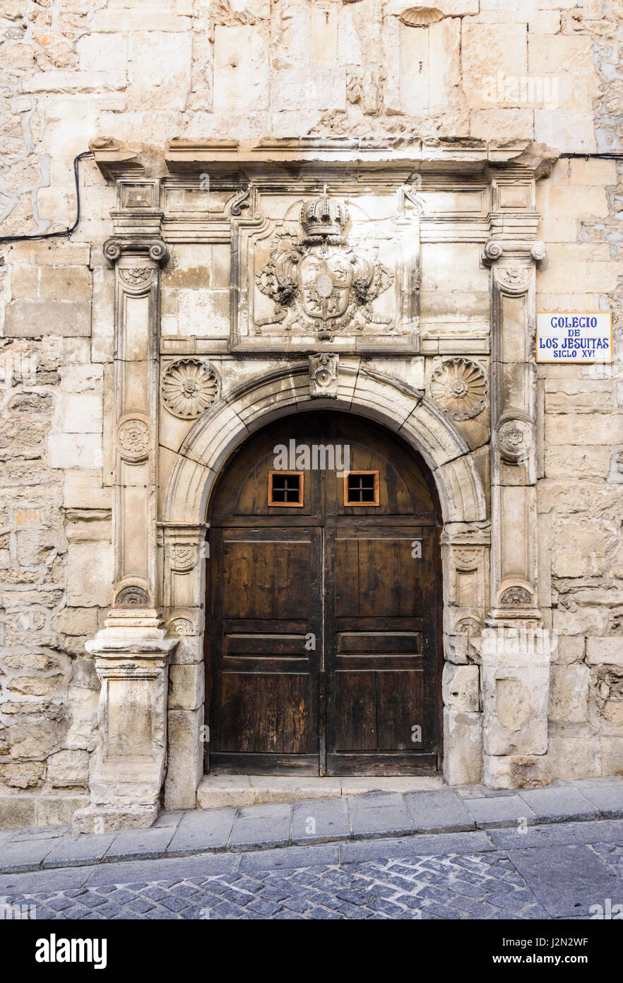 Wooden double doors and Jesuit coat of arms on the old Colegio de los Jesuitas, a historic building in the old medieval - Stock Image