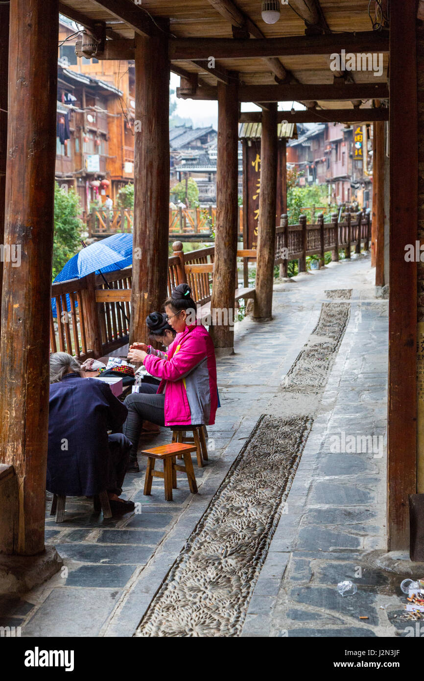 Zhaoxing, Guizhou, China, a Dong Minority Village.  Women Sewing in front of their House. Stock Photo