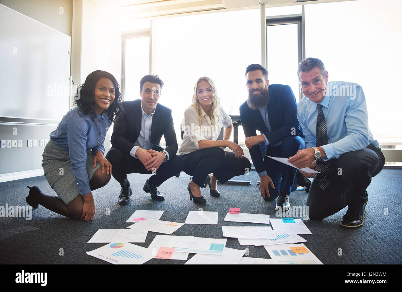 Smiling business team with ideas spread out on office floor Stock Photo