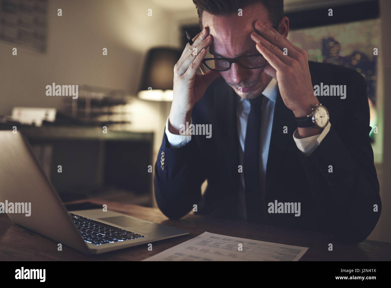 Thoughtful businessman sitting at the desk and working with the documents at night. - Stock Image
