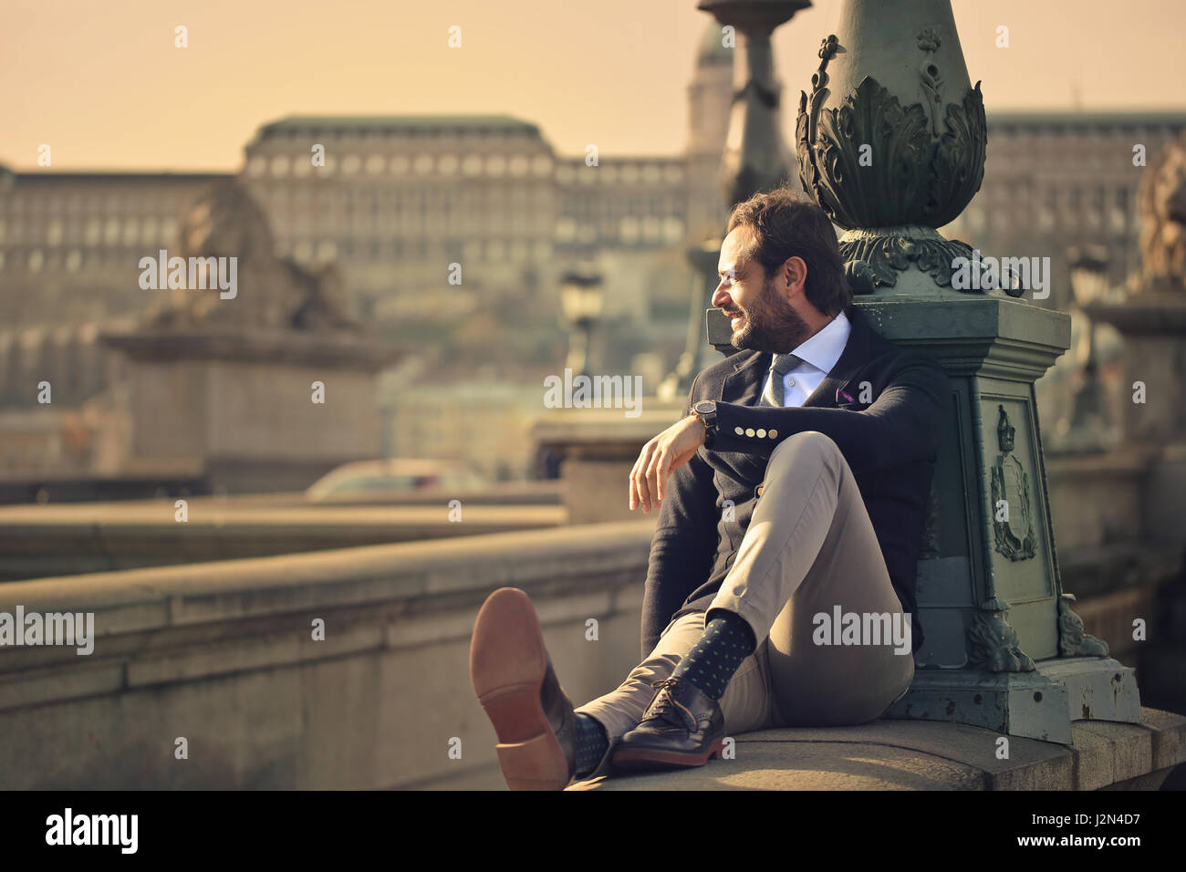Elegant man sitting in the city - Stock Image