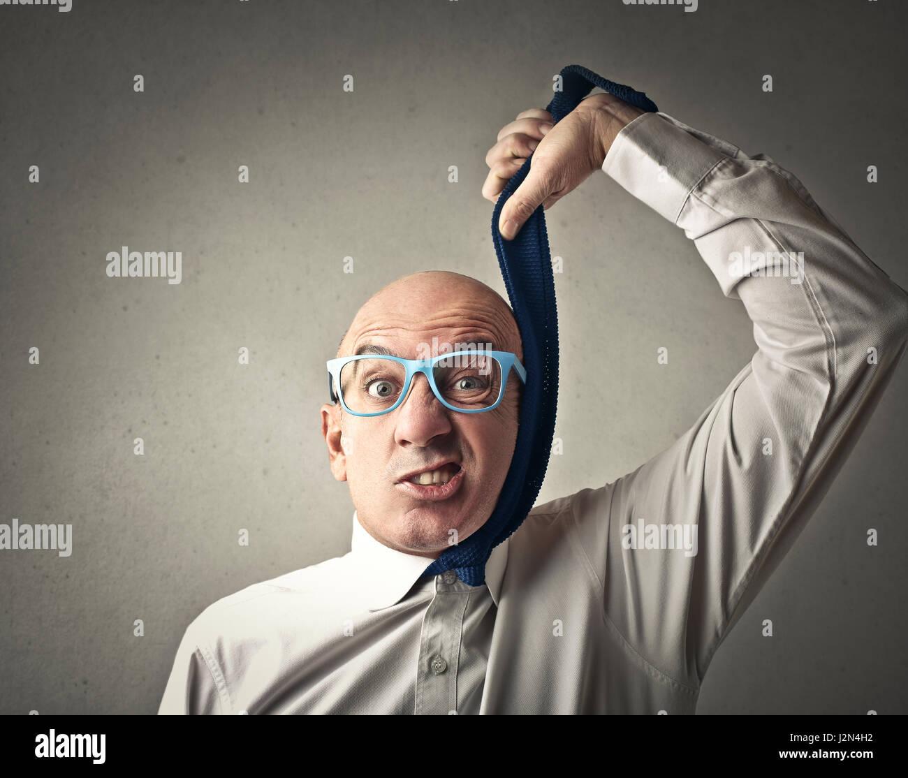Businessman choking himself with his tie - Stock Image