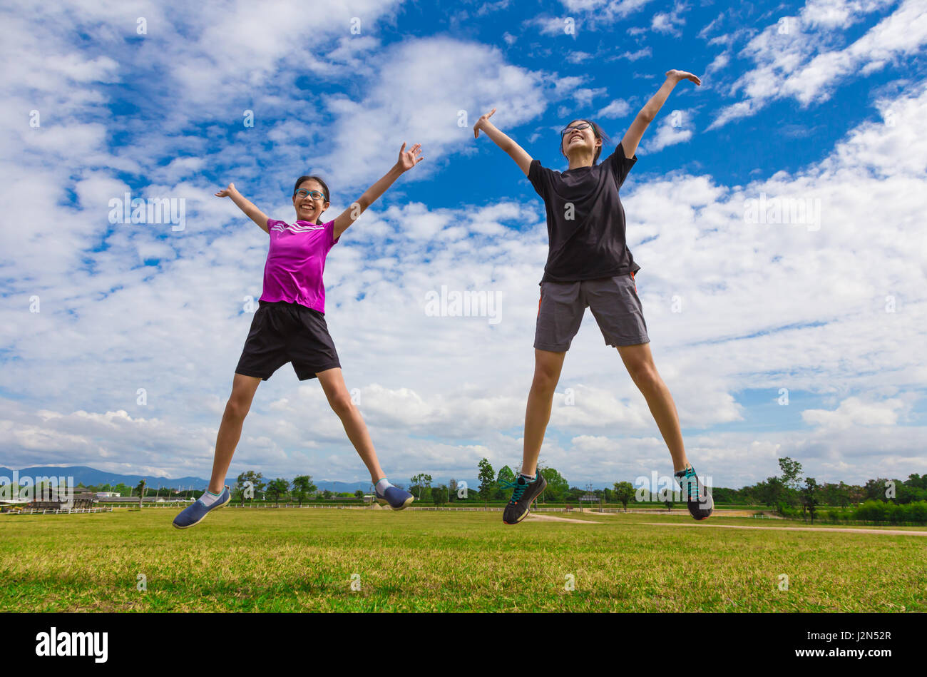 Two happy asian young teenagers jumping for joy in a grassy field on a bright sunny day with cloudy blue sky Stock Photo