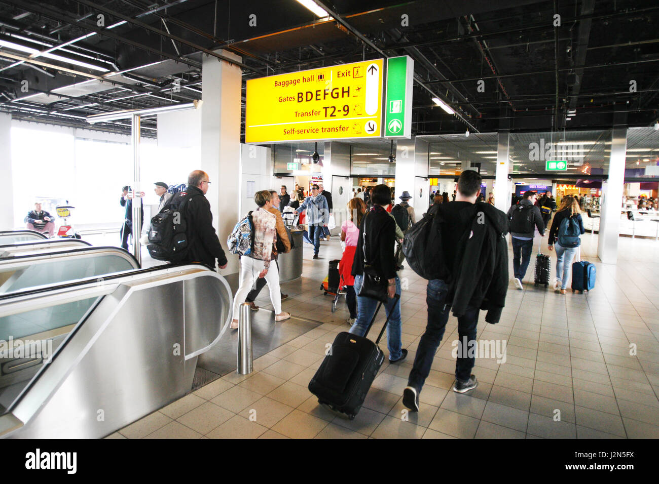 Travelers are seen in the arrival area at  Schiphol Airport on April 29, 2017 in Amsterdam, Netherlands. Schiphol - Stock Image