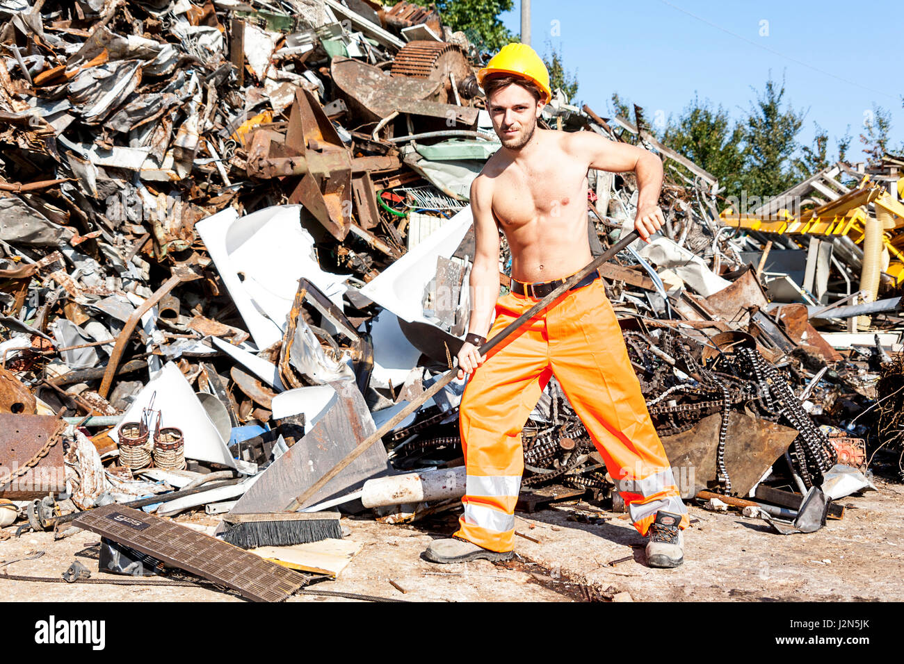 young worker in a junkyard - Stock Image