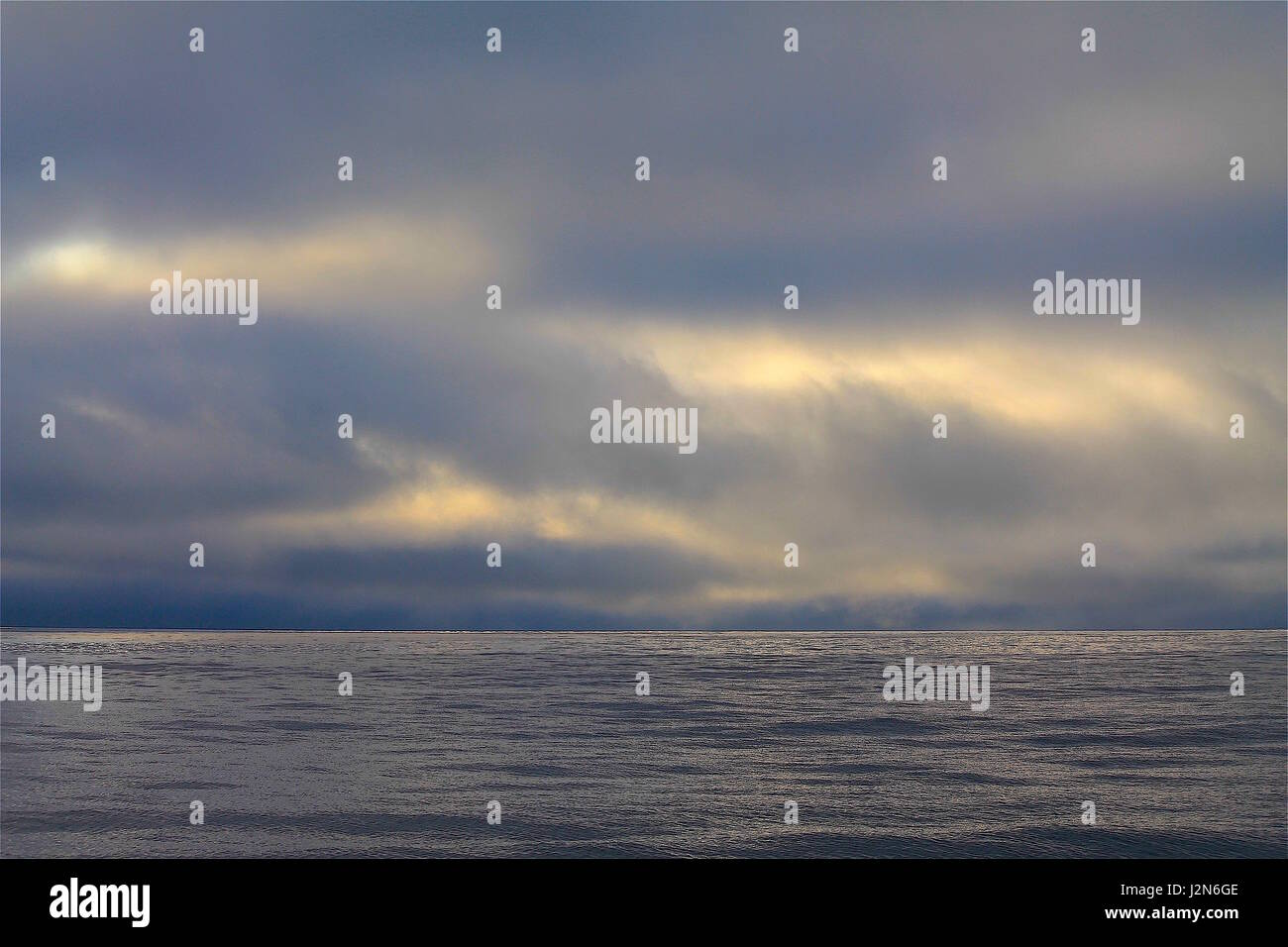 Overcast sunset at sea - Stock Image