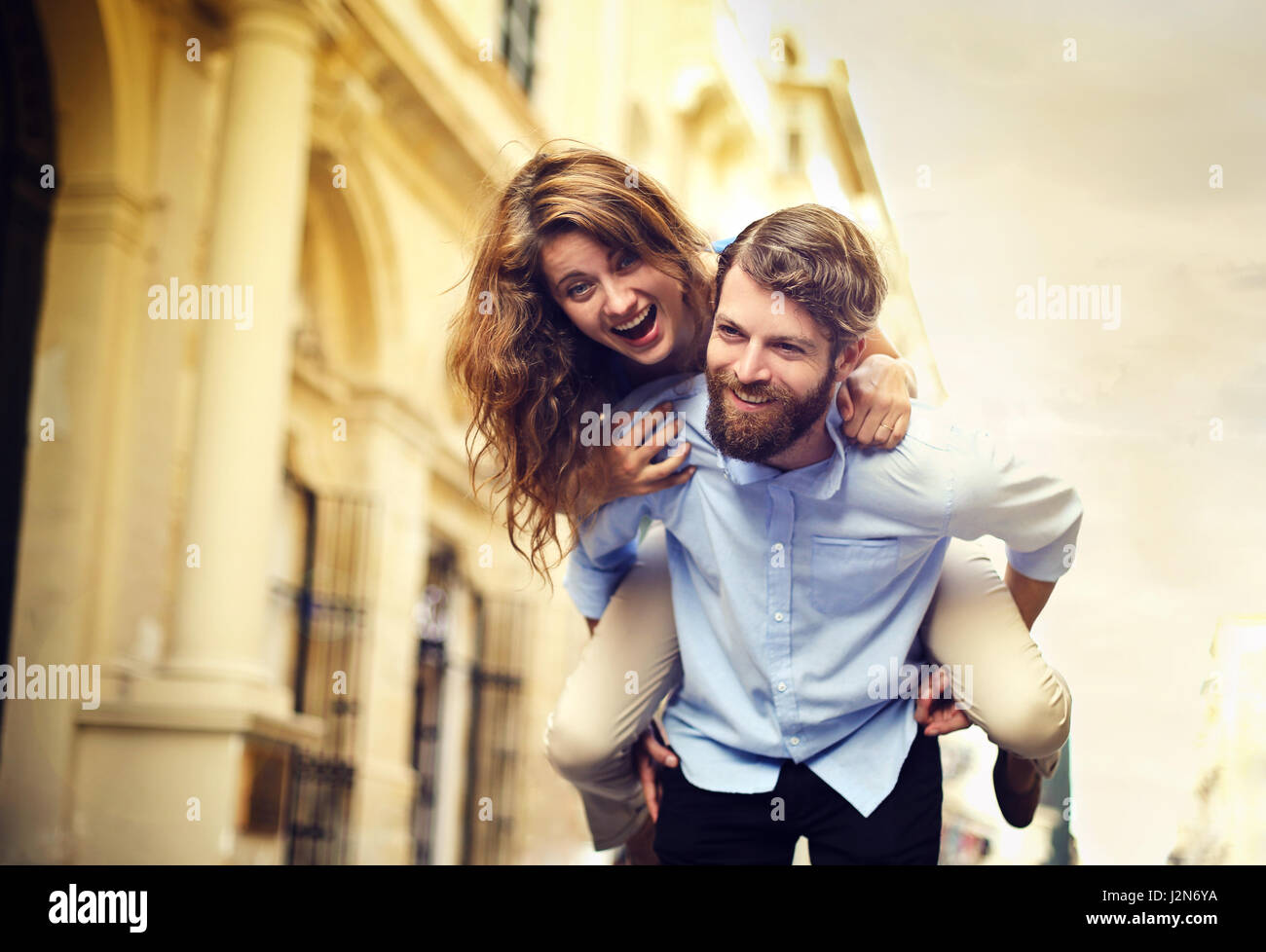 Man giving woman a piggy back - Stock Image