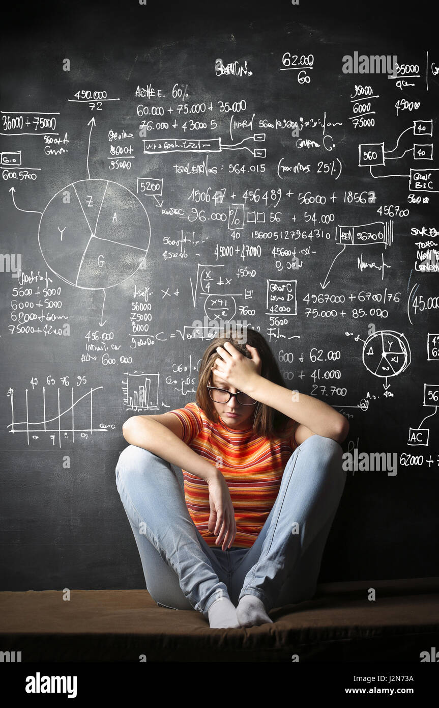 Depressed woman in front of chalkboard with notes - Stock Image
