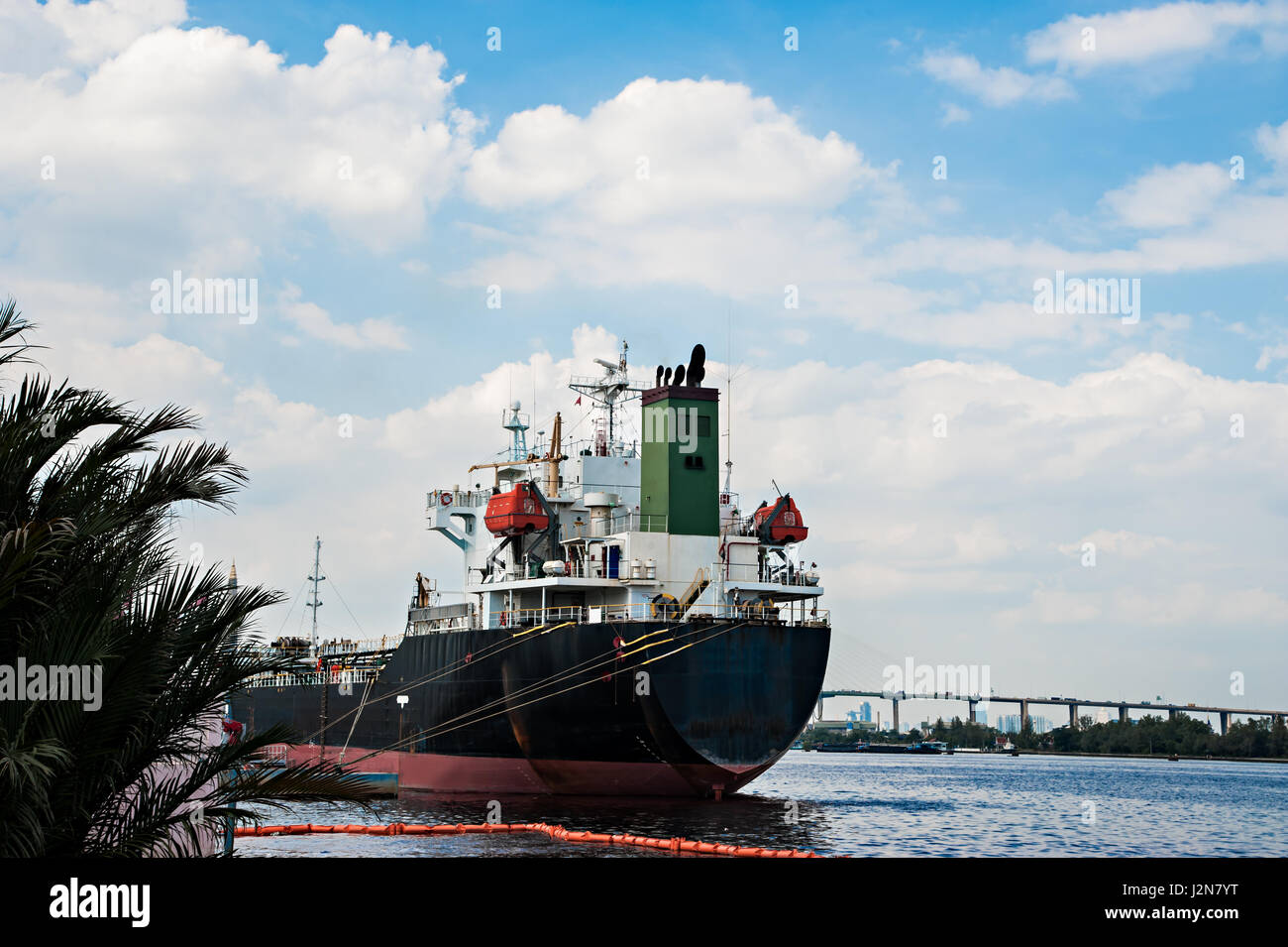 Logistic concept, black Ship parked in the river. Waiting to dock and load the goods. - Stock Image