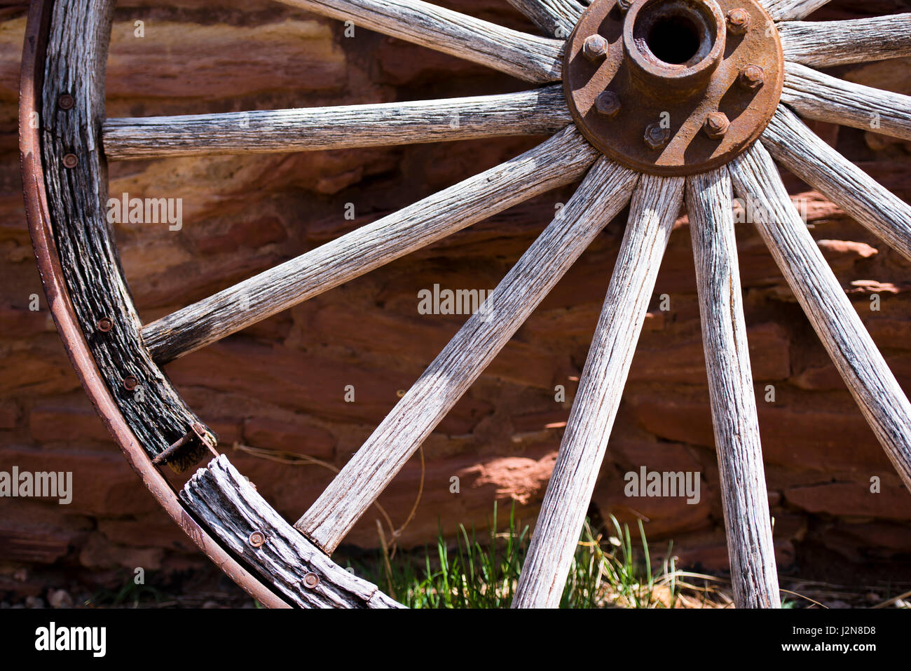 Detail of an old wooden wheel with rusty metal rim and the hub with bolts on the backdrop of a stone wall built - Stock Image