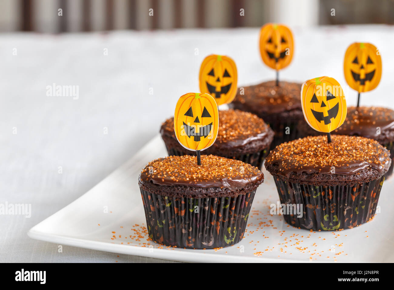 Chocolate Halloween cupcakes with orange decorations - Stock Image