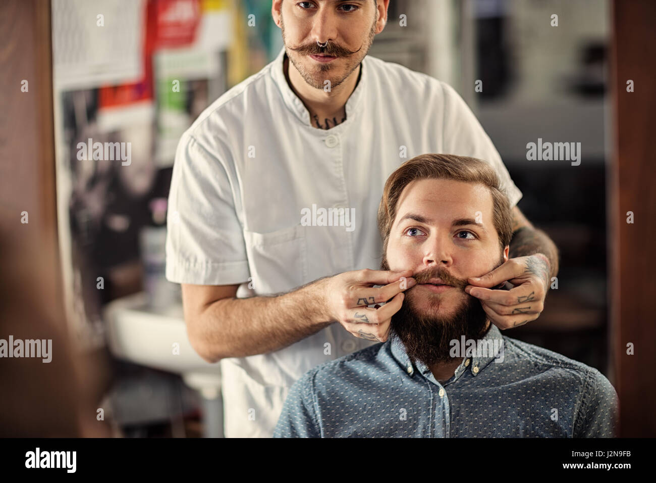 Skillful male barber is serving his client mustache - Stock Image