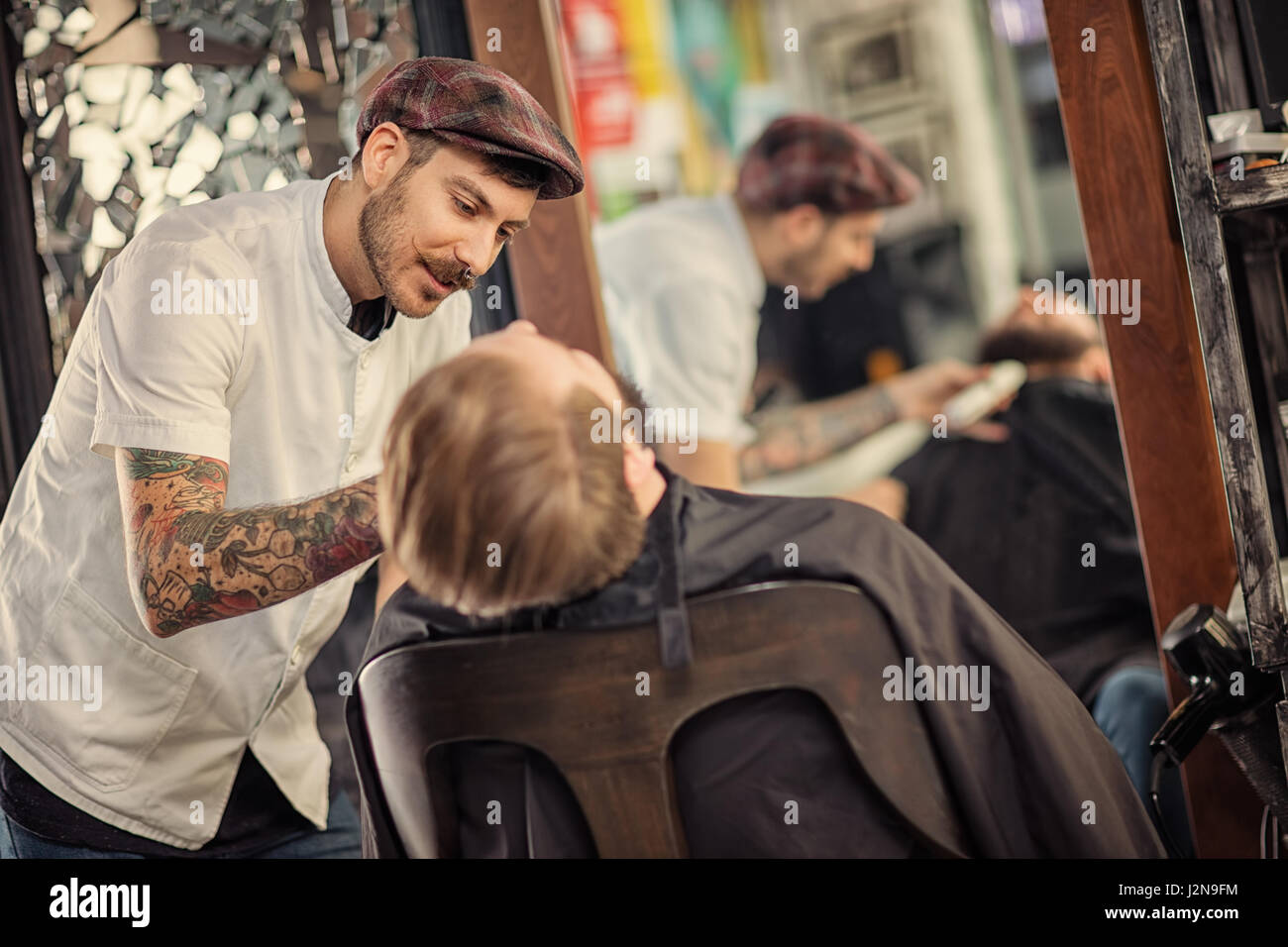 professional skillful barber shaving beard on customer - Stock Image