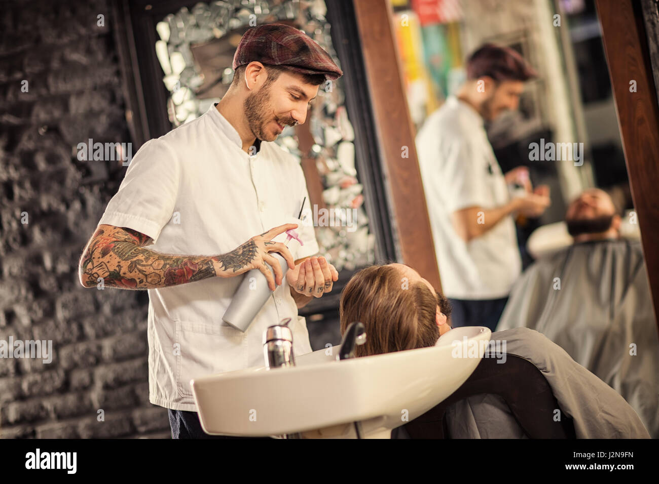 Hairstylist washing head of man with beard in barbershop - Stock Image