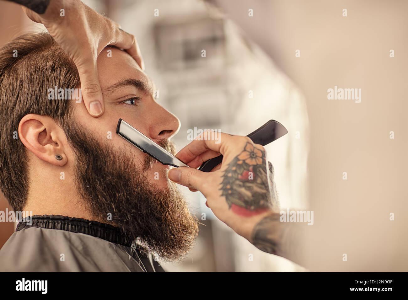 Barber with old-fashioned black razor shaving bearded man - Stock Image