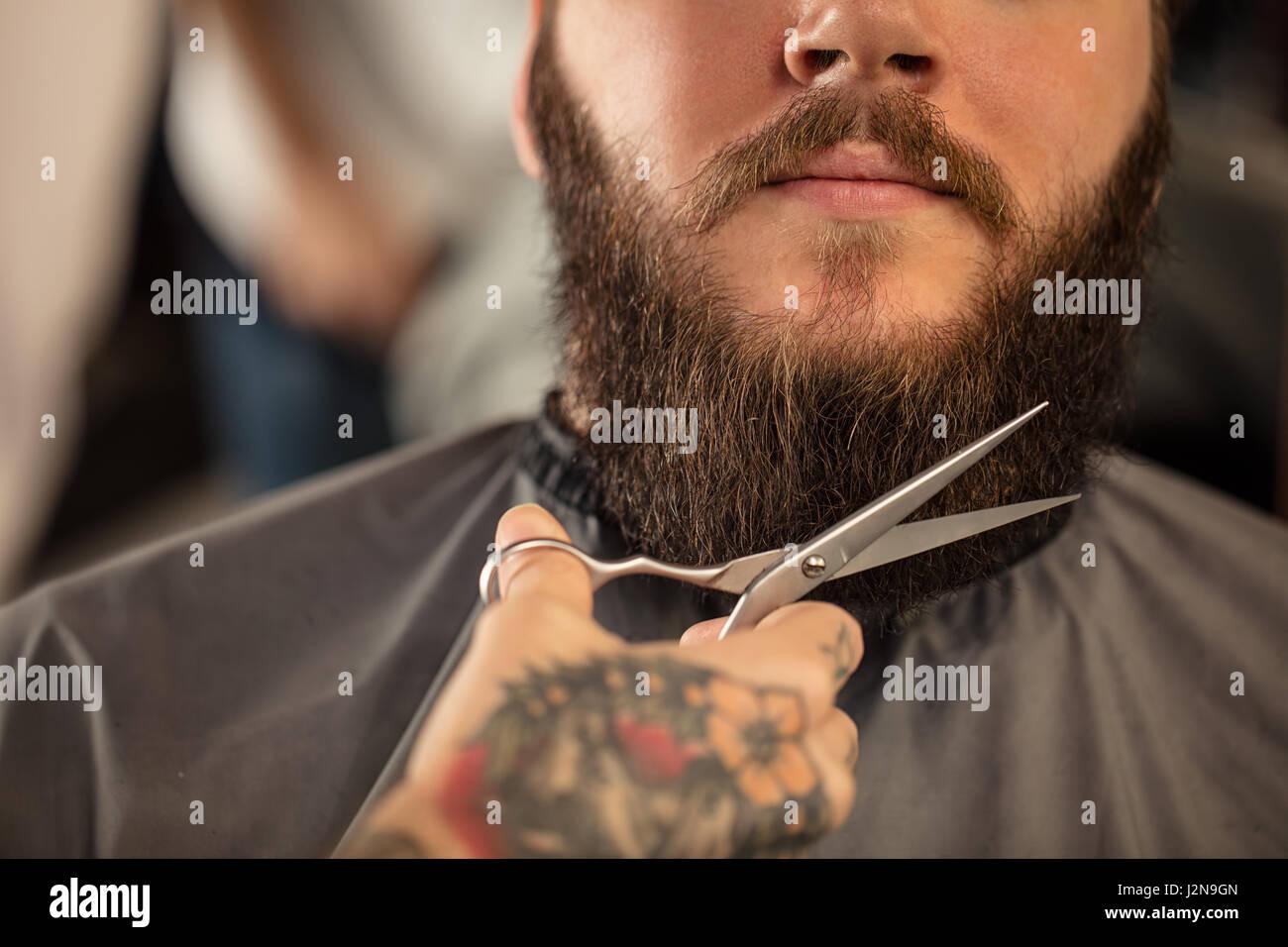 Barber with scissors shaving bearded man - Stock Image