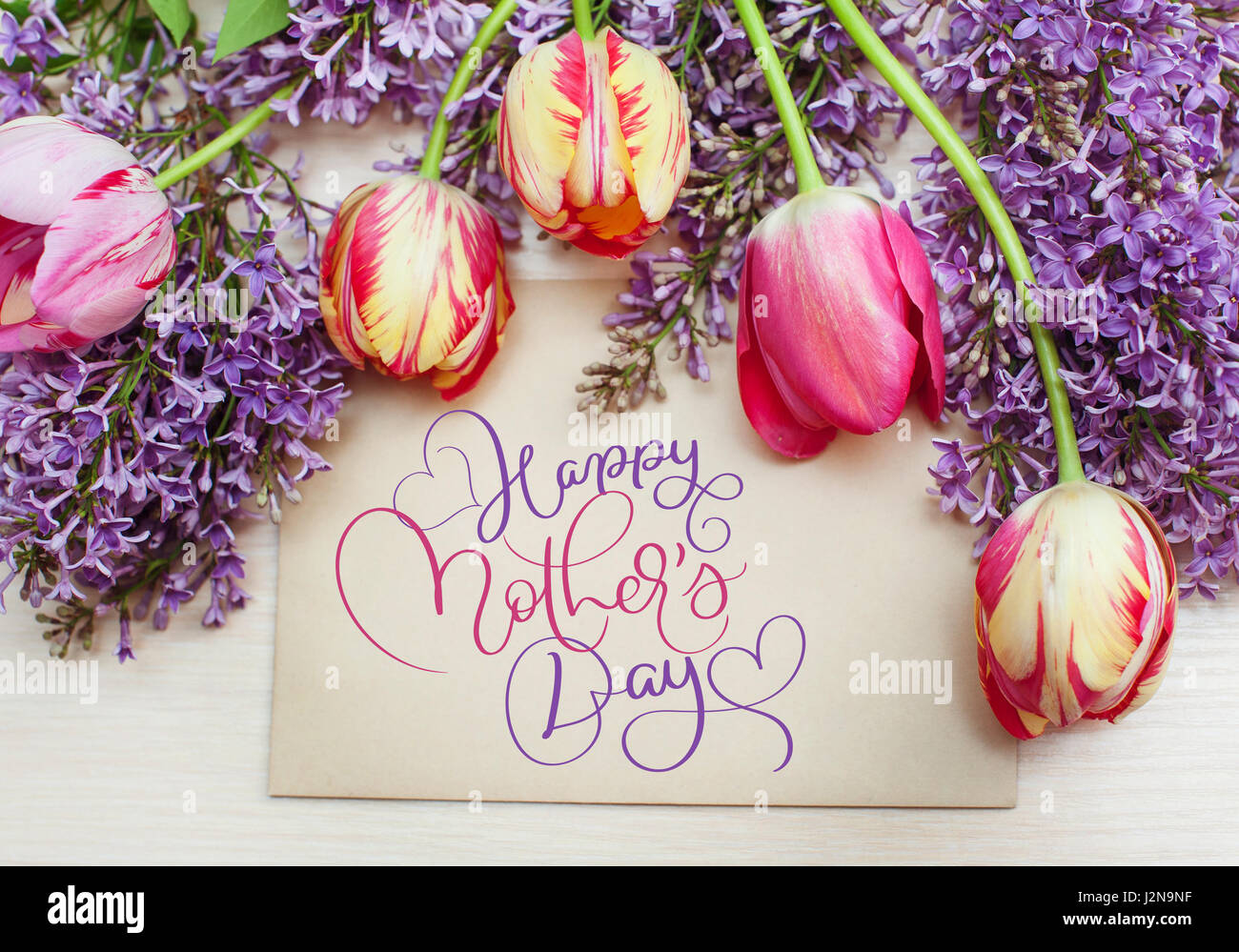 Frame from tulips and lilac and text happy mothers day. calligraphy