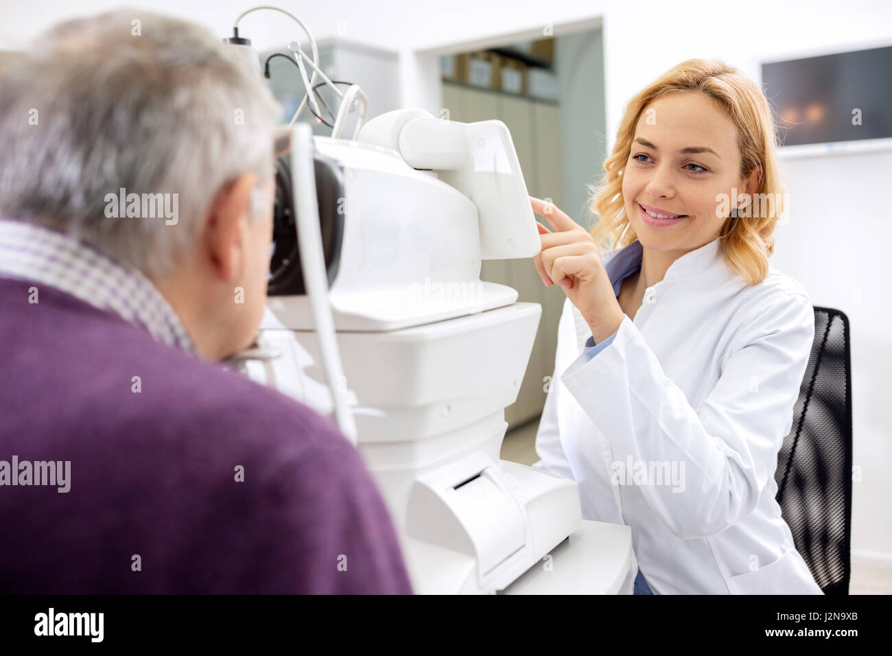 Young female eye doctor work with patient using eyes apparatus - Stock Image
