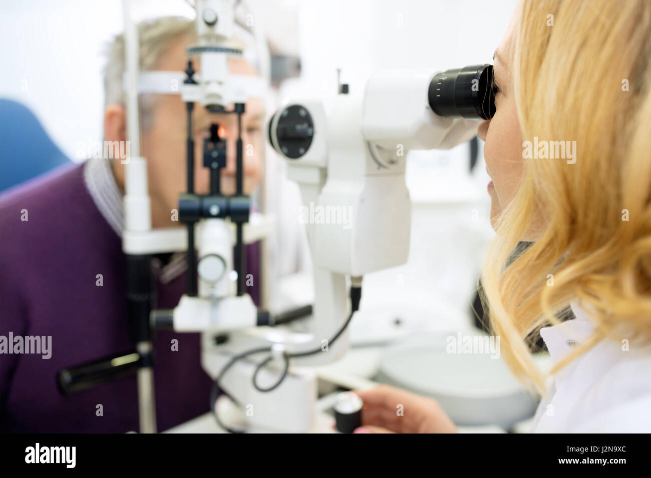 Female optical review of patient eyes with apparatus - Stock Image
