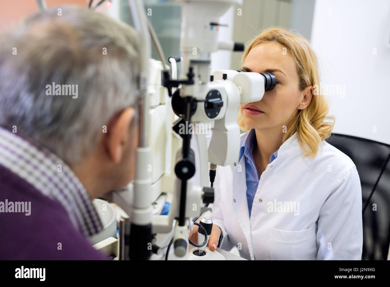 Patient eye doctor checkup patient eyes with apparatus - Stock Image