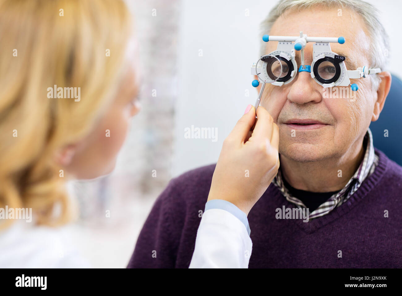 Optical specialists precisely determines diopter to senior male patient in clinic - Stock Image