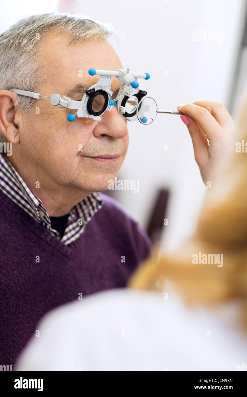 Ophthalmic doctor measure distance of eyes pupil in consulting room - Stock Image