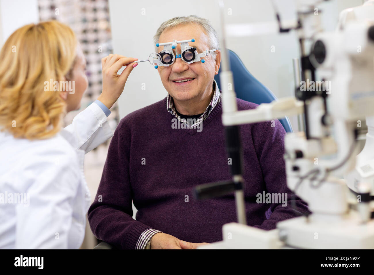Ocular female specialists work with patient in pleasant atmosphere on eye clinic - Stock Image