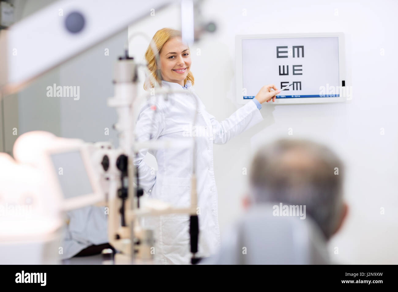 Nice female blonde eye doctor show letters in consulting room - Stock Image