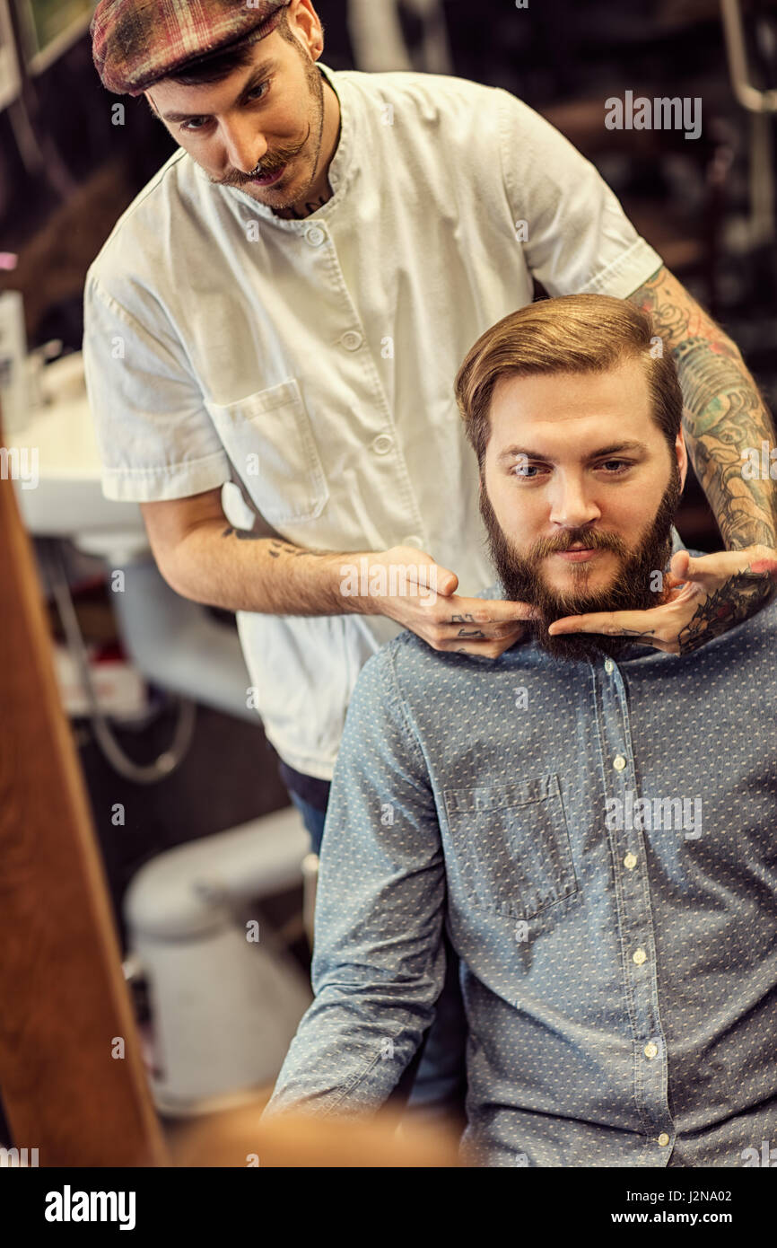 skillful barber making haircut too bearded customer at barbershop - Stock Image