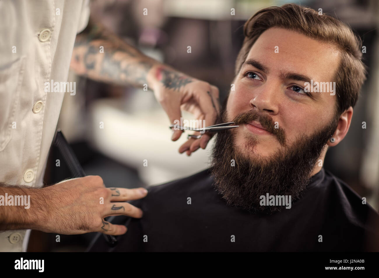 man barber with scissors cut the mustache smiling client - Stock Image