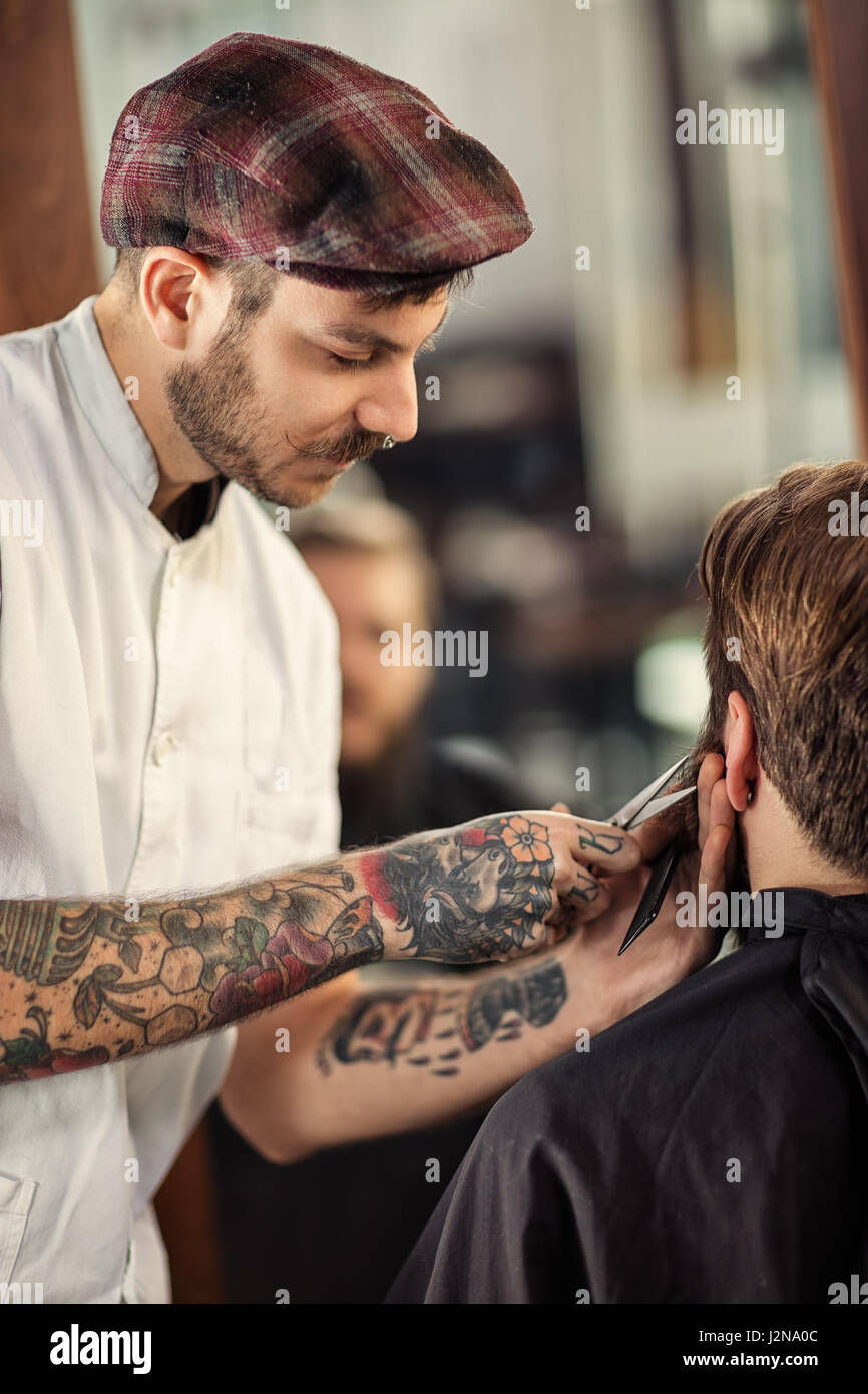 professional hairdresser with scissors cut the beard of client - Stock Image