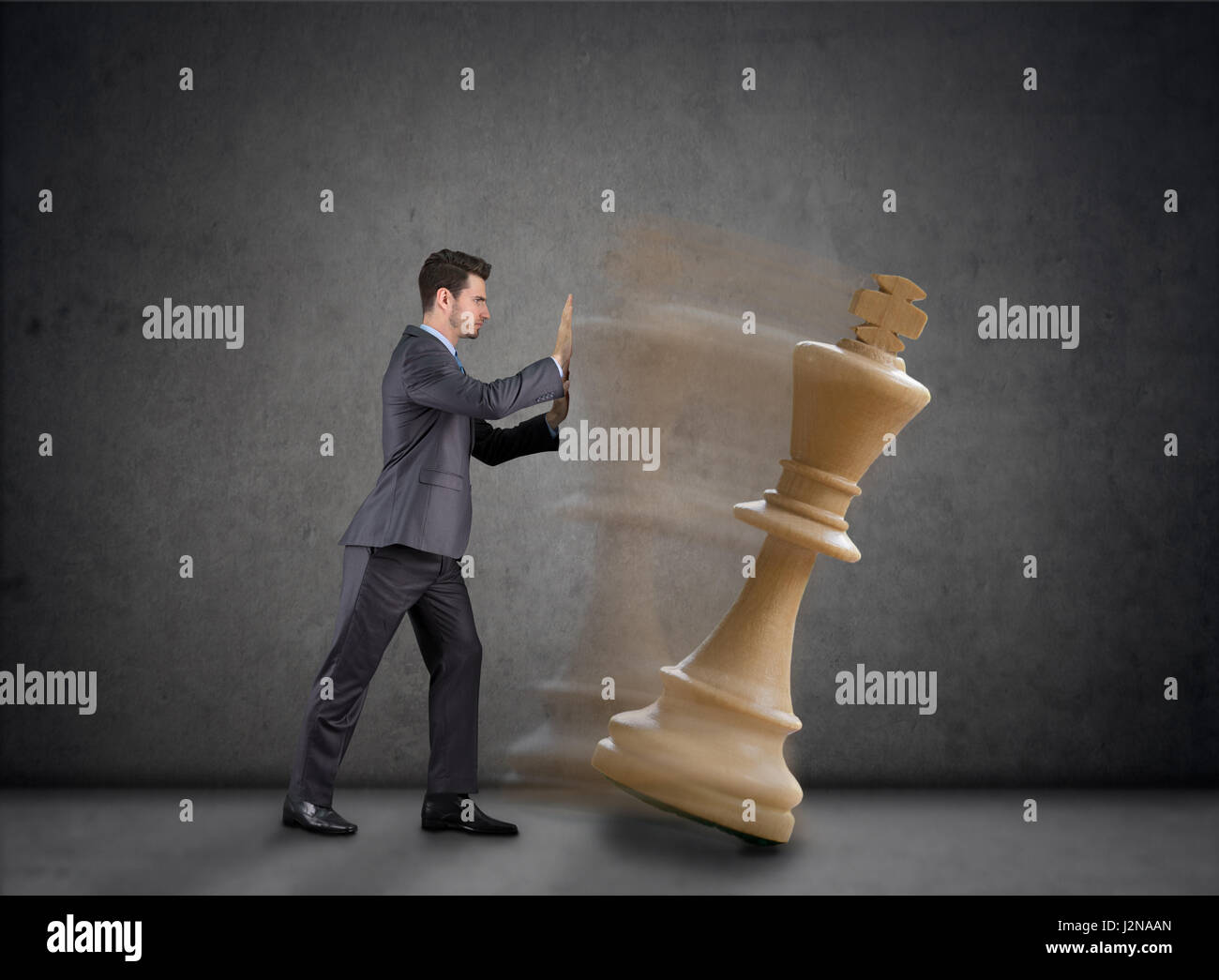 Businessman tear down the figure of Queen, strategy in business - Stock Image