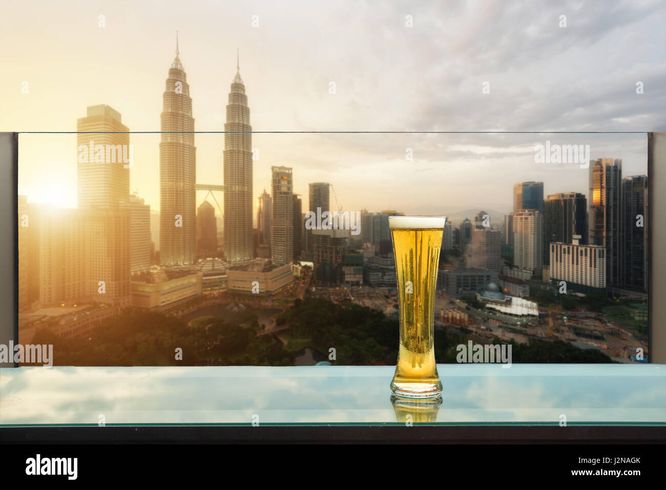 Beer and foam beer on table in rooftop bar with Kuala Lumpur skyscraper in background in Kuala Lumpur, Malaysia. - Stock Image