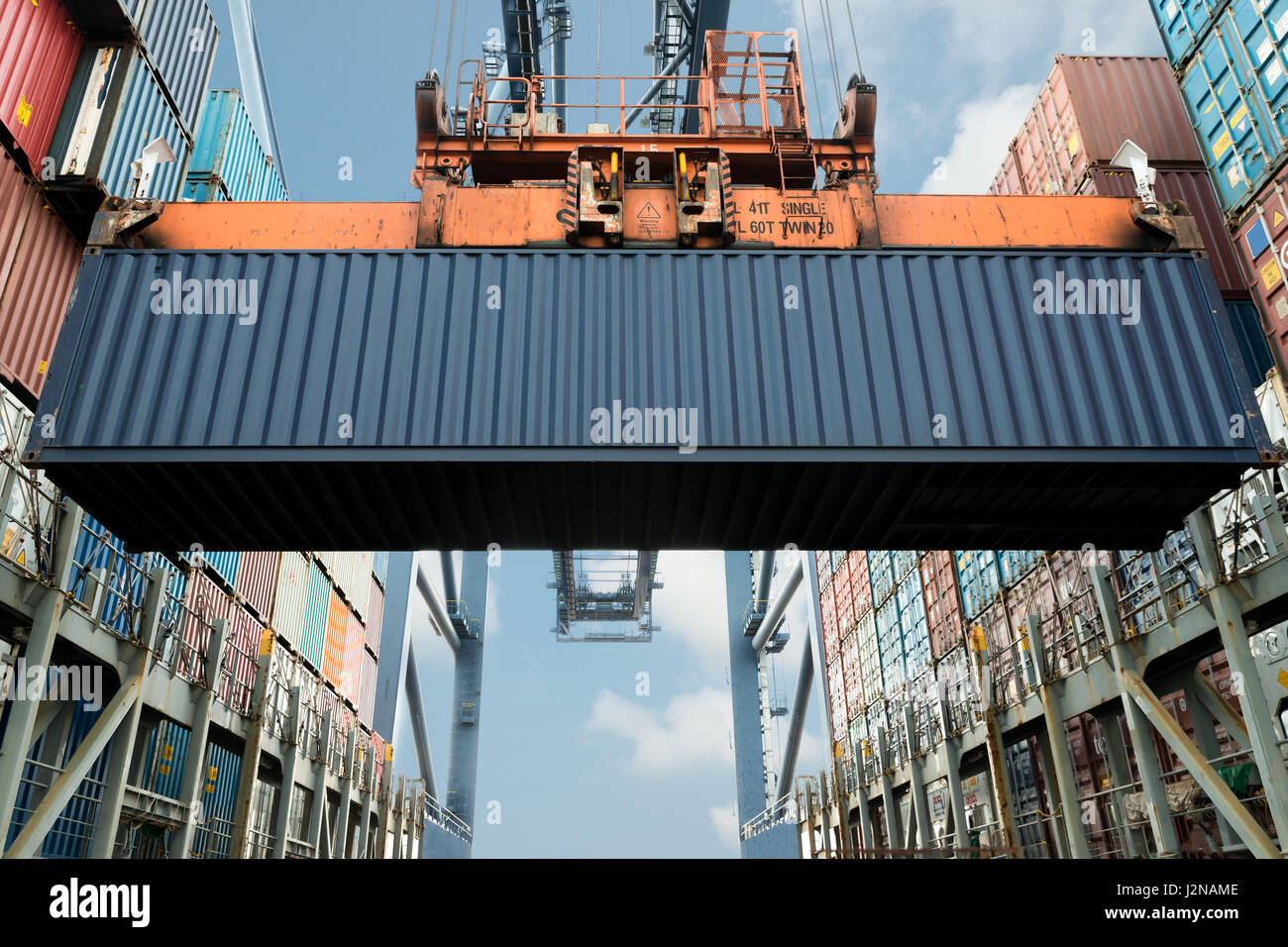 Shore crane loading export containers in freight ship use for import export and logistics background. - Stock Image