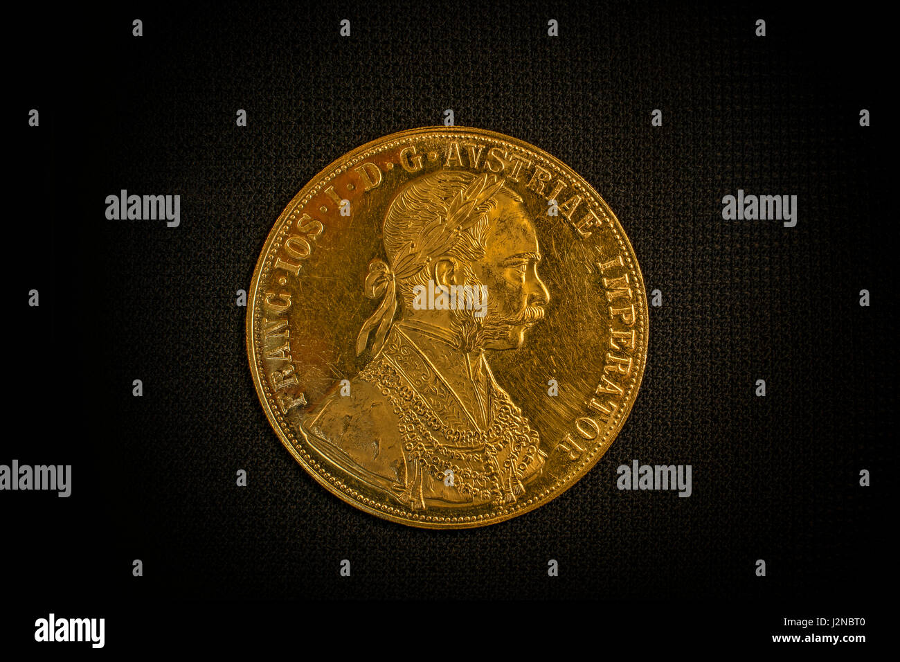 Close-up view of Austria-Hungary thaler, avers of golden coin-ducat from 1915 with Kaiser Franz Joseph I on dark - Stock Image