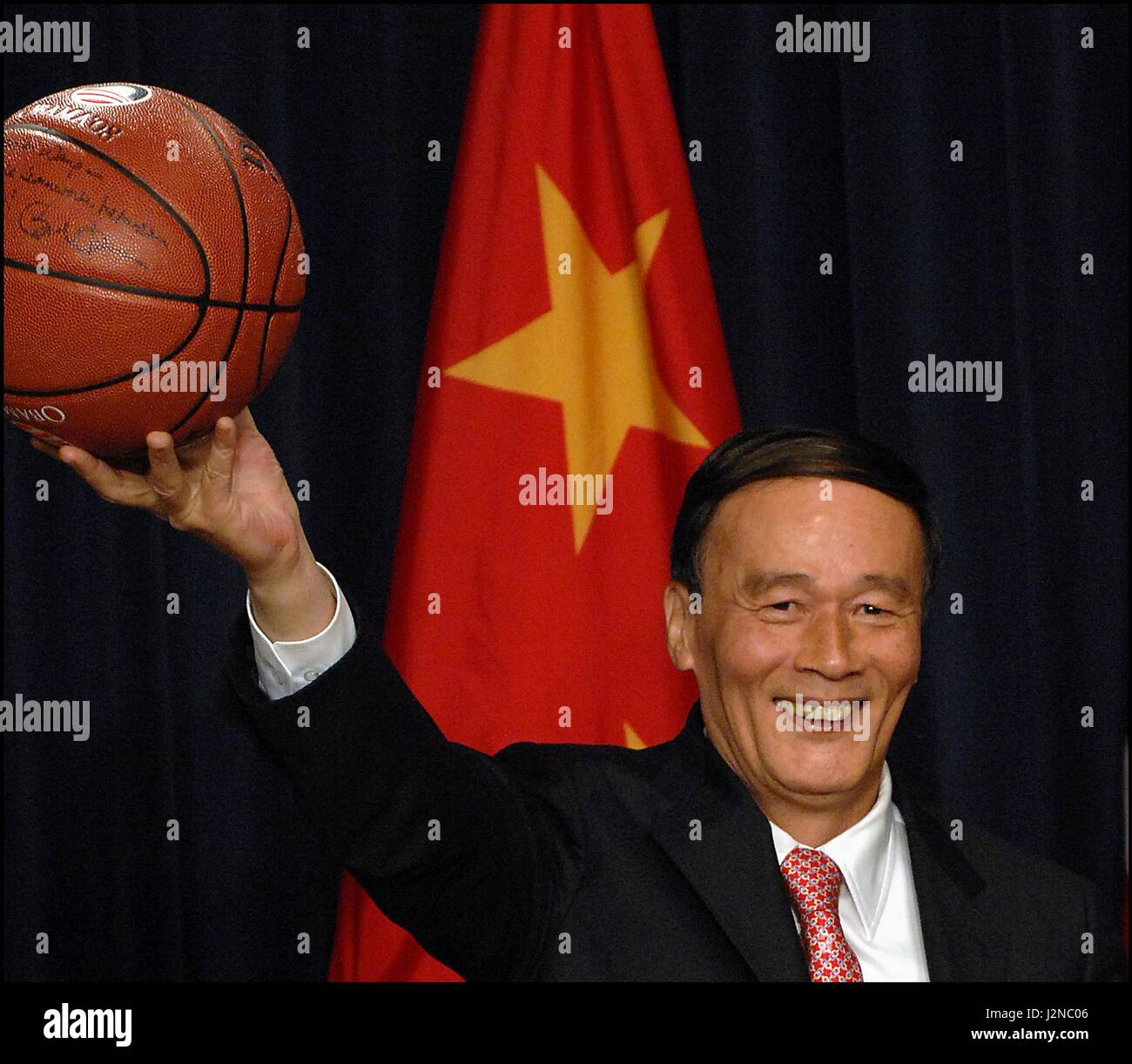 Chinese Vice Premier Wang Yang holds up a signed NBA basketball gifted him by U.S Treasury Secretary Timothy Geithner - Stock Image